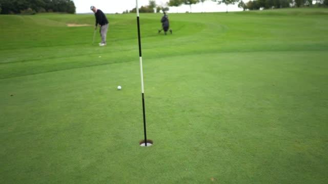 vídeos de stock, filmes e b-roll de a long putt in the hole. - bolsa de golfe