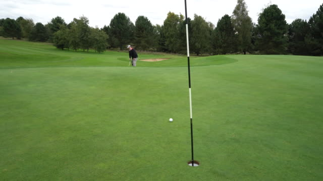 a long putt off the green only just misses the hole. - green golf course stock videos and b-roll footage