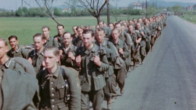 vidéos et rushes de long queue of captured german army soldiers marching along the roadside under white flag, shoes and boots tramping past - capitule