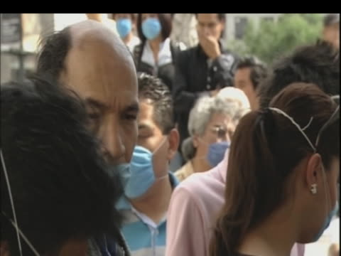 stockvideo's en b-roll-footage met long queue of mexicans wearing face masks wait in line for vaccinations following outbreak of swine flu mexico; 1 may 2009 - varkensgriep