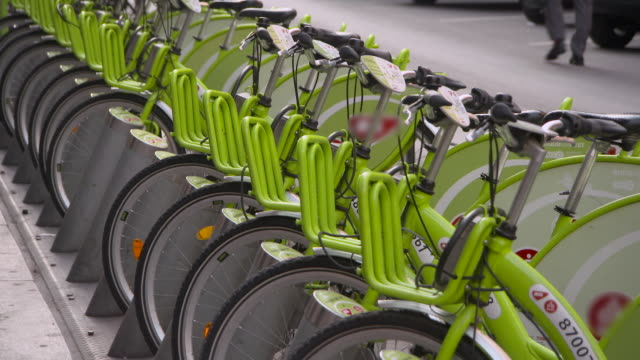 A Long Rack of Lime-Green Rental Bikes Stands On a Sidewalk