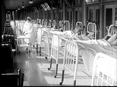1935 WS Long row of beds with patients tucked under white sheets/ Nurse pushing cart tending to patients/ AUDIO