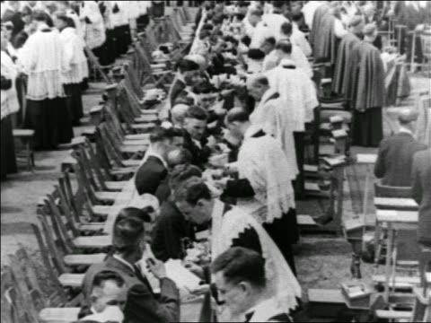 long row of couples + priests performing marriages in stadium / montreal / newsreel - priest stock videos & royalty-free footage