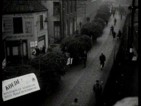 vídeos y material grabado en eventos de stock de long row of horse-drawn carriages with dead wood enters a city. the wood is divided among the people - tracción de caballos