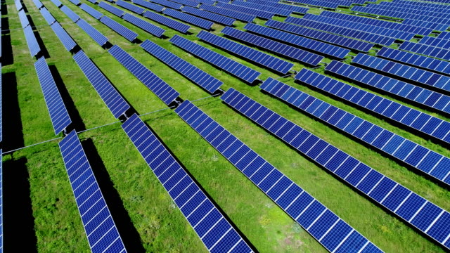 long rows of solar panels at webberville solar farm during springtime colorful - solar power station stock videos and b-roll footage
