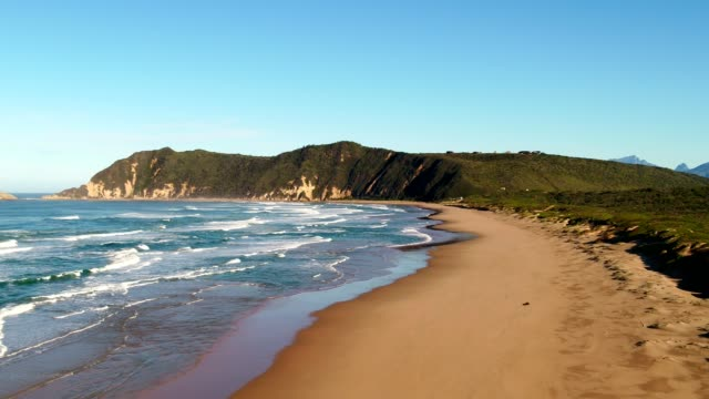 long sandy beach with waves in the bay of water - tide stock videos & royalty-free footage