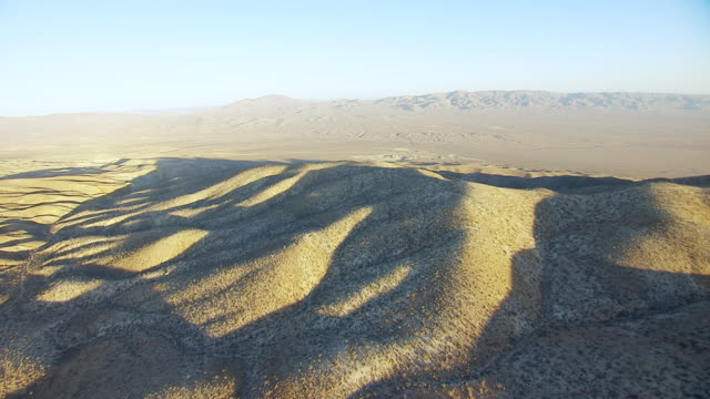 ws aerial pov long shadows on rolling foothills in desert valley with hills in background / california, united states - foothills stock videos & royalty-free footage