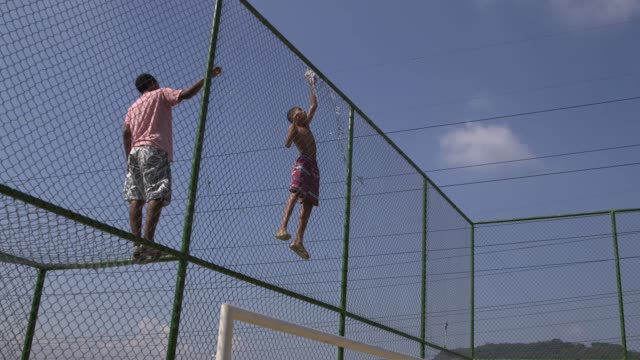 Long Shot a boy climbs up the football pitch fence to pick a kite that got stuck in the fence Children of the Morro da Sao Carlos favela play...