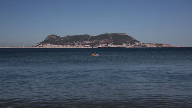 long shot a boy swims on a inflatable toy members of the public relax on a beach in front of the rock of gibraltar on august 7 2013 in algeciras... - gibraltar bildbanksvideor och videomaterial från bakom kulisserna