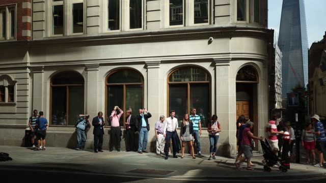 long shot a crowd gathers as the sun glares down from a new office building in the financial district on september 4 2013 in the city of london... - b roll stock videos & royalty-free footage