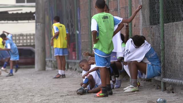 vidéos et rushes de long shot, a group of teenage boys are sitting on the bench and watching their friends play. children and teenagers play and train football in vila... - entraînement sportif