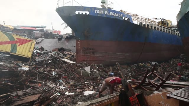 stockvideo's en b-roll-footage met long shot a man is sifting through the washed up debris and rubble for something useful typhoon haiyan which ripped through philippines on november 9... - goede staat