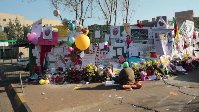 long shot, a man prays at the tribute wall to nelson mandela outside the mediclinic heart hospital where he is being treated for a lung infection on... - ハウテング州点の映像素材/bロール