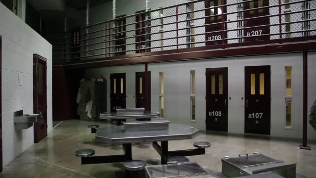 long shot, a military officer stands near prison cells in camp vi where prisoners are housed in a communal facility at the u.s. military prison for... - guantanamo bay stock videos & royalty-free footage