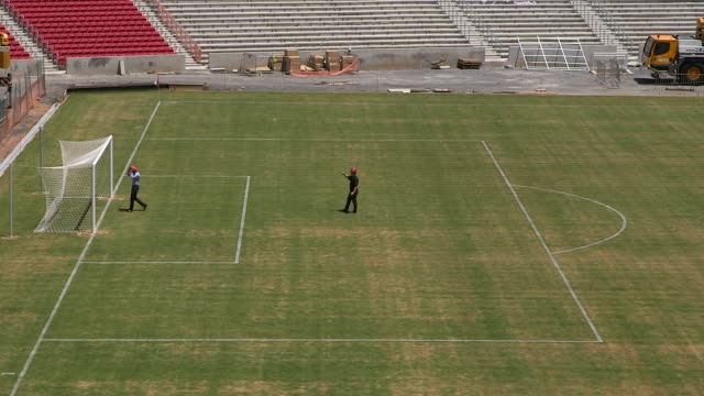 long shot a visitor posing for a photograph construction at estadio beirario in porto alegre continues home to the sport club internacional one of... - porto alegre stock-videos und b-roll-filmmaterial