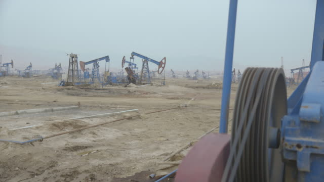 long shot across an operational oil field near baku. - baku video stock e b–roll