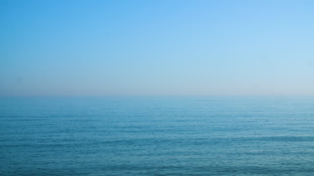 long shot across calm waters off brighton beach, uk. - wolkenloser himmel stock-videos und b-roll-filmmaterial