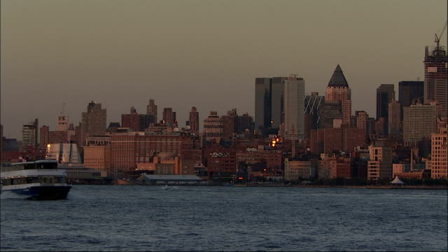 long shot across hudson river to manhattan island. ferry passes camera in foreground - dusk. new york. available in hd. - ferry stock videos & royalty-free footage