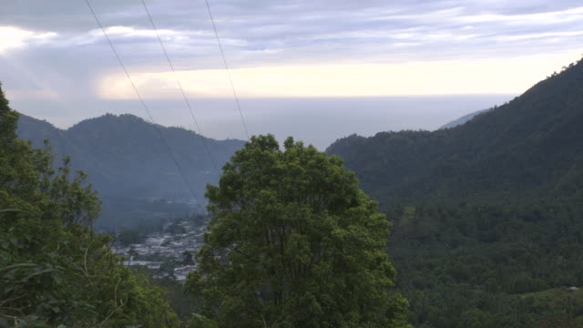 Long shot across the forested mountains of Anjouan towards the city of Domoni.
