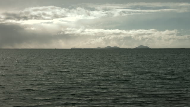 Long shot across water towards distant mountains on the coastline of southern Iceland.