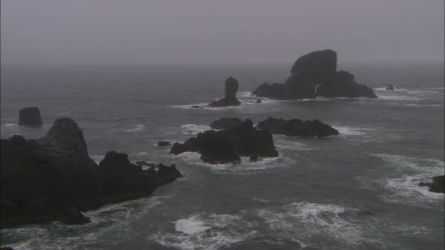 long shot aerial - ocean waves crash against rock formations beneath a gray sky - coastal feature stock videos & royalty-free footage