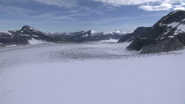 """Long Shot aerial pan-left push-in tilt-down-Deep snow blankets a remote, glacial landscape in Alaska. / Alaska, USA"""