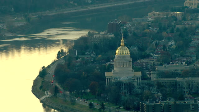 long shot aerial pan,left zoom,out , a river winds past a gold domed building and village. / west virginia - dome stock videos & royalty-free footage
