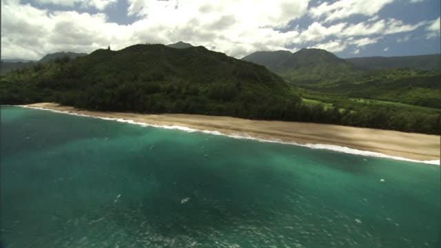 Long Shot aerial push-in tracking-left - Pacific waves roll onto the coast of Hawaii's Kauai island. / Hawaii, USA