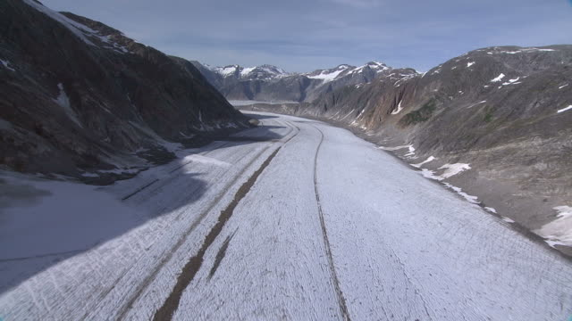 'Long Shot aerial push-in-Snow and ice blankets a river winding through mountains. / Alaska, USA'