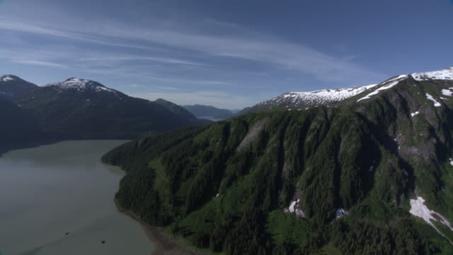 """long shot aerial push-in-snow fills crevices of  lush alaskan mountains  where a wide river snakes past. / alaska, usa"" - crevice stock videos & royalty-free footage"
