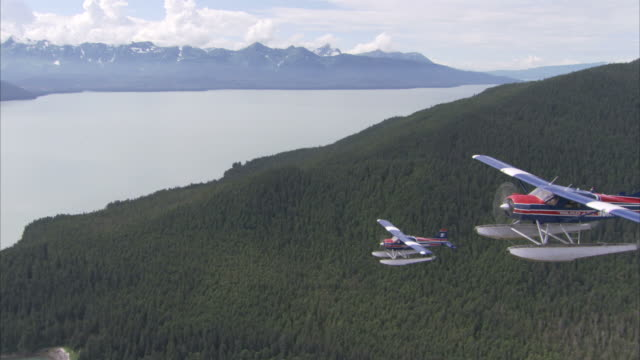 """long shot aerial tracking-left-seaplanes fly above forested alaskan mountains. / alaska, usa"" - air to air shot stock videos and b-roll footage"