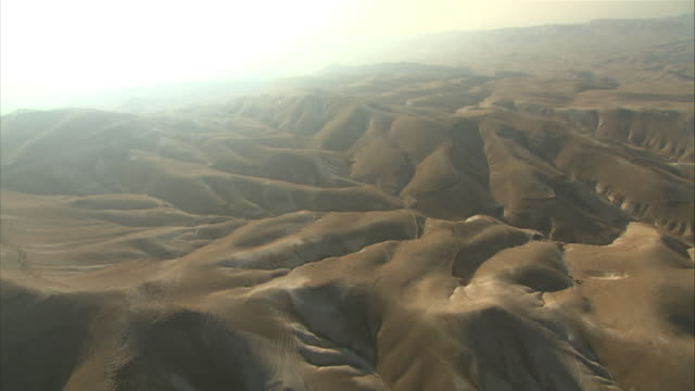long shot aerial tracking-right - rolling hills stretch toward a distant horizon in israel.  - ausgedörrt stock-videos und b-roll-filmmaterial