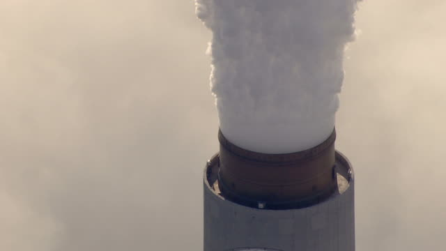 Long Shot aerial tracking,right zoom,out , A dense column of smoke rises from a coal plant smokestack. / West Virginia