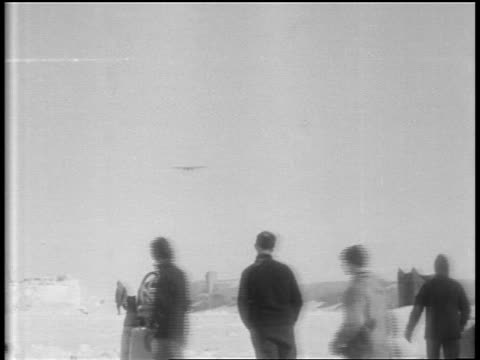 b/w 1929 long shot airplane ascending over snowy plain / people walking in foreground / antarctica - 1929 stock videos and b-roll footage