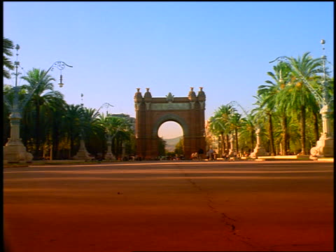 long shot Arc del Triomf in square with palm trees / Barcelona, Spain