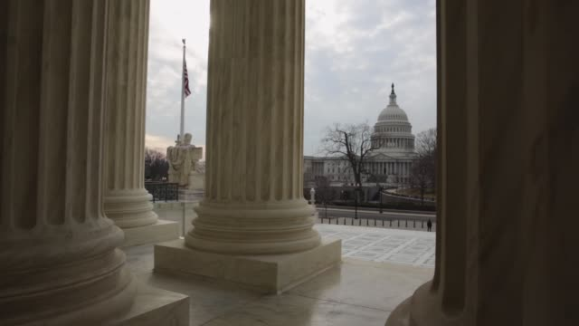long shot as the us capitol is seen in the background a us flag flies between columns of the us supreme court washington dc february 7 2014 - oberstes bundesgericht der usa stock-videos und b-roll-filmmaterial