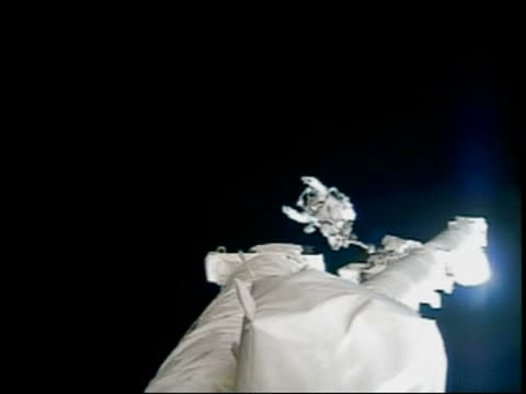 vídeos de stock, filmes e b-roll de 2005 long shot astronaut tethered to canadarm2 at the international space station waving / sts114 - só um homem maduro
