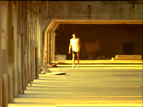 sepia long shot black male athlete stretching on cement floor of building - manipolazione di colore video stock e b–roll