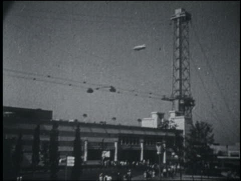 b/w 1933 long shot blimp flying cable cars moving over building / chicago world's fair - 1933 stock videos & royalty-free footage