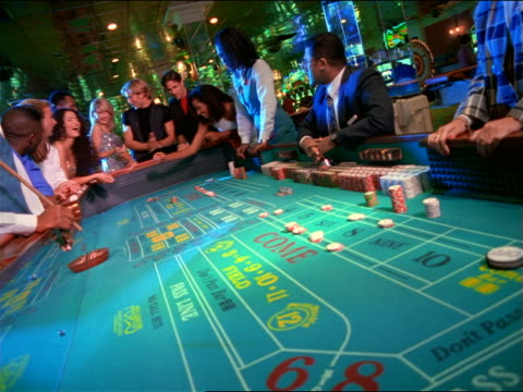 canted long shot blonde woman in sequined dress rolling dice at craps table as cheering friends watch - craps stock videos & royalty-free footage