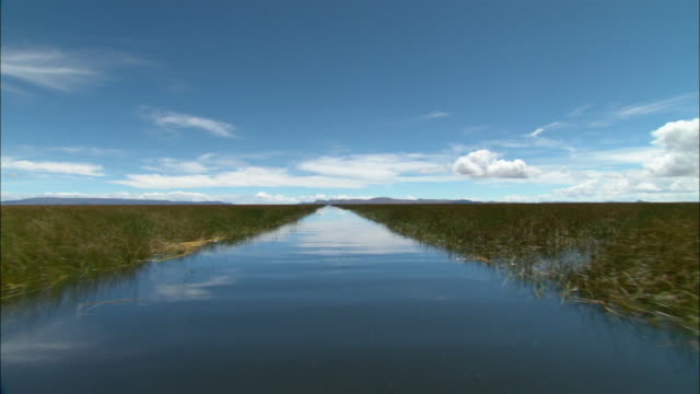 long shot boat point of view through reed bed in lake titicaca / sky reflected on surface of water / puno, peru - boat point of view stock videos & royalty-free footage