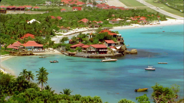 vidéos et rushes de long shot boats on turquoise water in harbor with buildings on penisula / st. barts - antilles occidentales