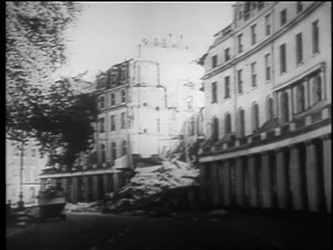 vidéos et rushes de long shot bombed out building surrounded by standing buildings after london blitz / educational - 1940