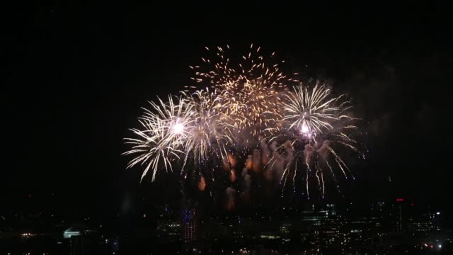 long shot, boston at night. fireworks explode over the charles river with the city of cambridge, massachusetts in the background as revelers... - firework display stock-videos und b-roll-filmmaterial