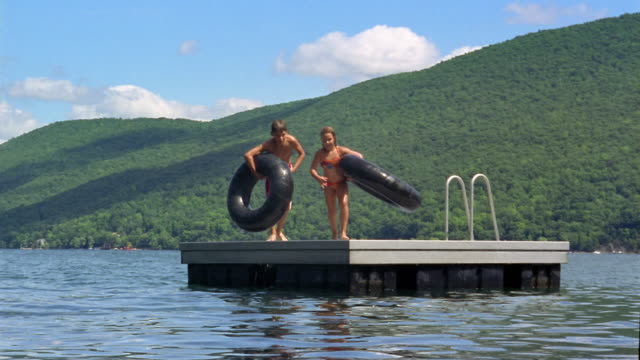 stockvideo's en b-roll-footage met long shot boy and girl jumping off raft with inner tubes / canandaigua lake, new york - zwembroek