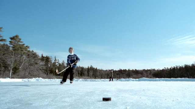 long shot boy skating to hockey puck in foreground on frozen pond / hitting puck to friend in background / maine - eislaufen stock-videos und b-roll-filmmaterial