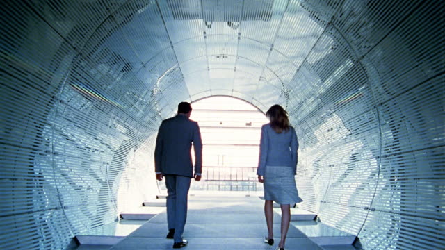Long shot businessman and woman walking in tunnel + through glass doors / Berlin