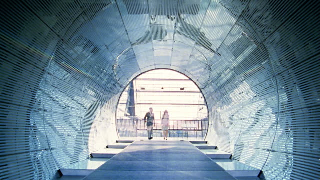 vidéos et rushes de long shot businessman and woman walking through glass doors + into tunnel / berlin - au loin