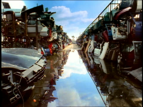 long shot car scraps piled on both sides of wet road in junkyard - zerstörung stock-videos und b-roll-filmmaterial