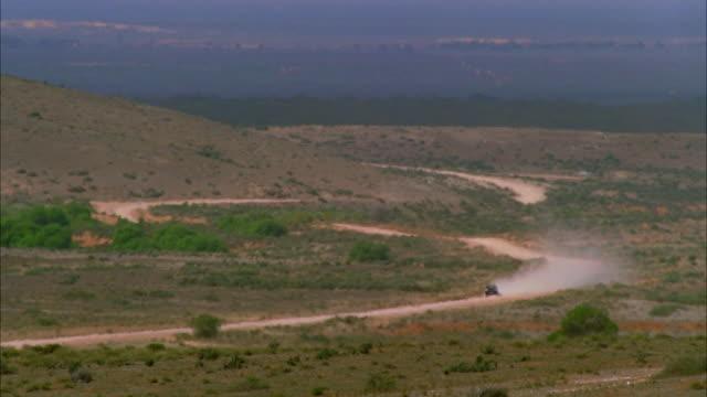 long shot car speeding along switchbacks on dusty desert road - distant stock videos & royalty-free footage